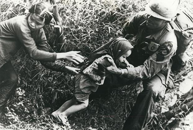 Американский пехотинец помогает бежать женщине и ребенку из района боевых действий во Вьетнаме, 1967 год