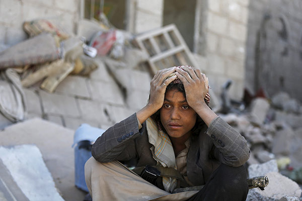 A member of the Houthi group sits on the rubble of houses destroyed by an overnight Saudi-led air strike on a residential area in Yemen's capital Sanaa May 1, 2015. At lease 14 people, including 10 women and a girl were killed and more than 50 injured in the strike that destroyed six houses in Sa'awan residential area, police said. REUTERS/Khaled Abdullah