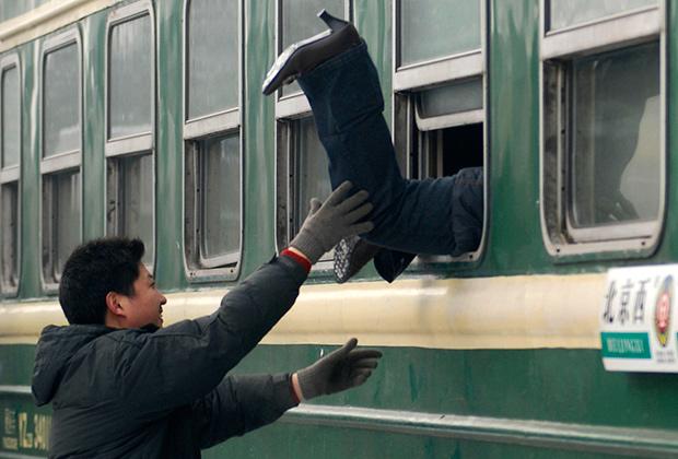 Китаец помогает женщине залезть в окно поезда на железнодорожной станции в провинции Шаньси. 14 января 2008