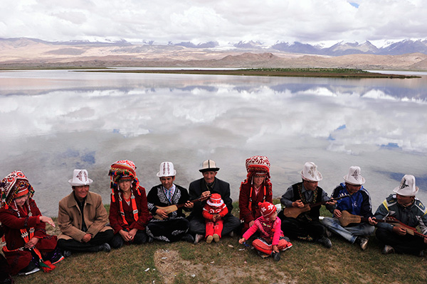 2012An ethnic Tajik family plays traditional musical instruments as they pose for a video during their family gathering near Karakul Lake at the foot of Muztag Ata, at Pamirs in Xinjiang Uighur Autonomous Region