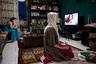 Женщина молится, пока ее подруга курит и смотрит телевизор.