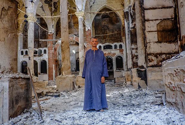 Копт в одной из сожженных и разрушенных коптских церквей в провинции Минья, 2013 год