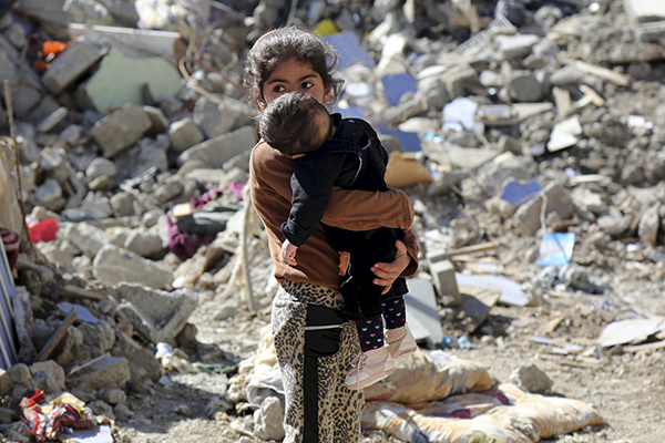 A girl carries a baby as she walks in the debris of buildings, which were damaged during the security operations and clashes between Turkish security forces and Kurdish militants, in the southeastern town of Cizre in Sirnak province, Turkey March 2, 2016. REUTERS/Sertac Kayar