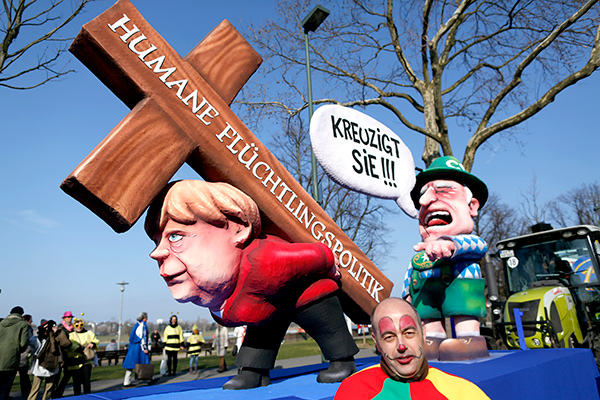 "A carnival float with papier-mache caricatures mocking Bavarian Governor Horst Seehofer and German Chancellor Angela Merkel is displayed at a postponed ""Rosenmontag"" (Rose Monday) parade, at one location in Duesseldorf, Germany, March 13, 2016, after the original parade in February was cancelled due to severe weather. Words read 'crucify her' 'human politics for migrants'. REUTERS/Ina Fassbender"
