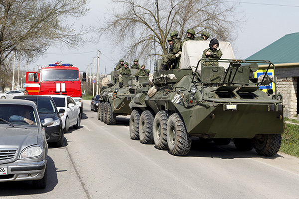 Servicemen of the Russian armed forces ride on armoured vehicles in a settlement of the Novoselitsky district, where a local police station was recently attacked, in Stavropol region, southern Russia, April 11, 2016. REUTERS/Eduard Korniyenko - RTX29FAJ