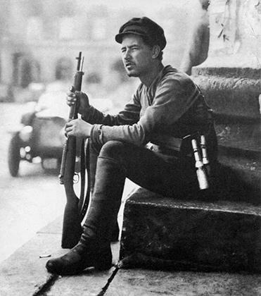 Красногвардеец И.А. Раснянский у Большого театра после подавления левоэсеровского мятежа в Москве. В его руках карабин «Арисака» Тип 38, на поясе – ручные гранаты образца 1914 года. Июль 1918 года