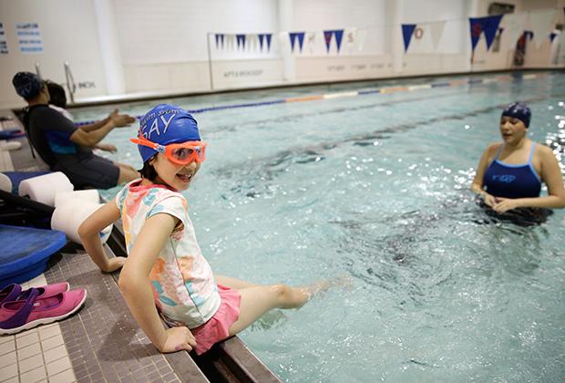 Девочка с аутизмом готовится прыгнуть в бассейн во время урока плавания в реабилитационном центре Нью-Йорка