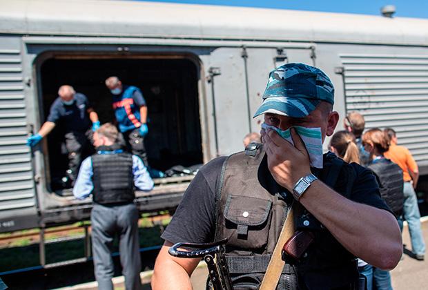 Сотрудники миссии ОБСЕ и эксперты из Нидерландов осматривают вагон с телами погибших в авиакатастрофе