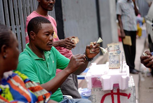 В обменных пунктах Киншасы деньги часто лежат прямо на полу