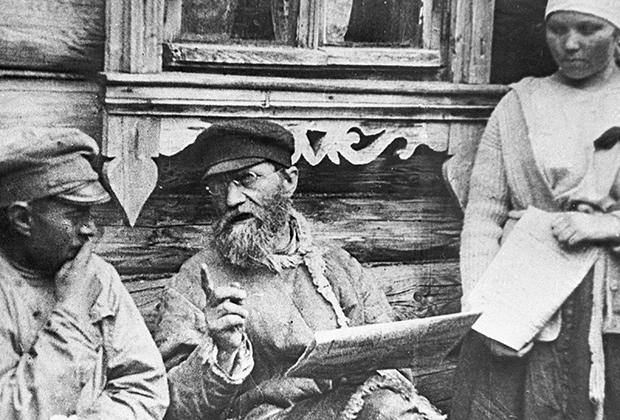 Крестьяне читают газету, в которой опубликованы ленинские декреты о земле и мире