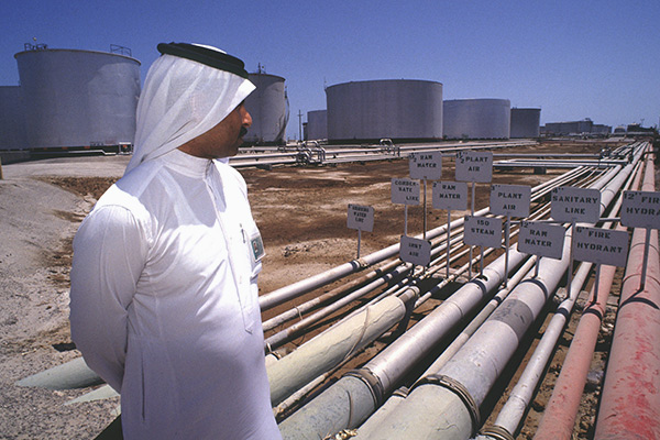 WWJ ras tanura, saudi arabia -- a saudi official looks over oil pipelines feeding the largest crude oil refinery in the world. © Barry Iverson / Alamy