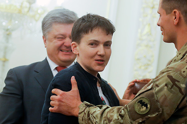 Ukrainian President Petro Poroshenko,  left, smiles, as Ukrainian jailed pilot Nadezhda Savchenko, center is congratulated by servicemen of the Aidar battalion, in the Presidential Office in Kiev, Ukraine, Wednesday, May 25, 2016. Russia has released jailed pilot Nadezhda Savchenko, as part of a swap for two Russian servicemen imprisoned in Ukraine. (AP Photo/Efrem Lukatsky)