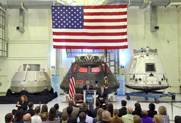 Глава НАСА Чарльз Болден и директор Космического центра Кеннеди Боб Кабана на фоне прототипов разрабатываемых пилотируемых космических кораблей Orion, Dragon V2 и CST-100