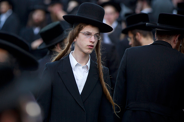 An Ultra-Orthodox Jew attends a prayer as he and others gather in the religious neighborhood of Mea Shearim to protest against summer events organized by the city council, Jerusalem