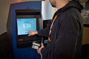 A customer uses the world's first ever permanent bitcoin ATM unveiled at a coffee shop in Vancouver, British Columbia October 29, 2013. The kiosk, built by Las Vegas RoboCoin and operated by local dealer Bitcoiniacs, will allow users to withdraw their bit coins in the form of Canadian dollars or deposit cash to buy more bitcoins.  REUTERS/Andy Clark    (CANADA - Tags: SOCIETY BUSINESS SCIENCE TECHNOLOGY) - RTX14SYF
