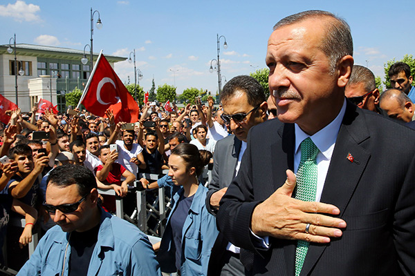 In this Friday, July 22, 2016 photo, Turkey's President Recep Tayyip Erdogan, acknowledges the crowd as he arrives at the parliament in Ankara, Turkey. Turkish lawmakers approved a three-month state of emergency that allows the government to extend detention times and issue decrees without parliamentary approval. (Press Presidency Press Service via AP, Pool)