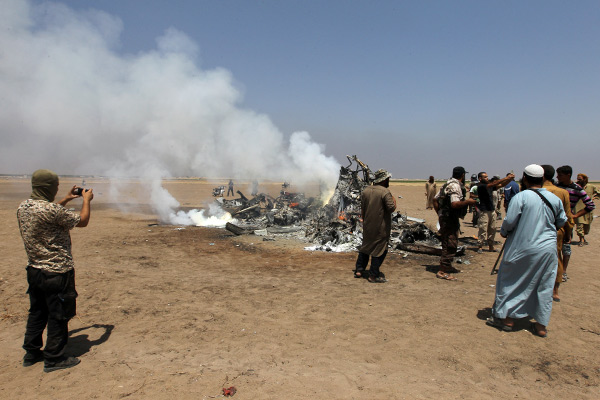 Rebel fighters and civilians inspect the wreckage of a Russian helicopter that had been shot down in the north of Syria's rebel-held Idlib province, Syria August 1, 2016. REUTERS/Ammar Abdullah - RTSKJ0U