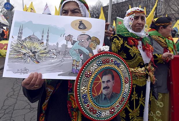 Прокурдская демонстрация в Ганновере. В руках участницы карикатура, изображающая Эрдогана и Меркель, а также портрет лидера РПК Оджалана. 19 марта 2016 года