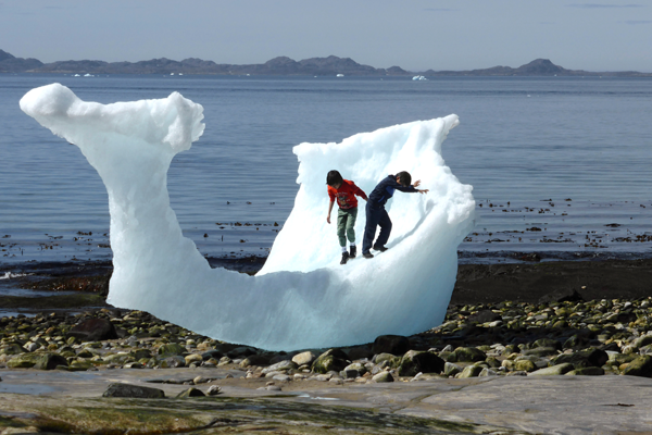 Children play amid icebergs on the beach in Nuuk, Greenland, June 5, 2016. REUTERS/Children