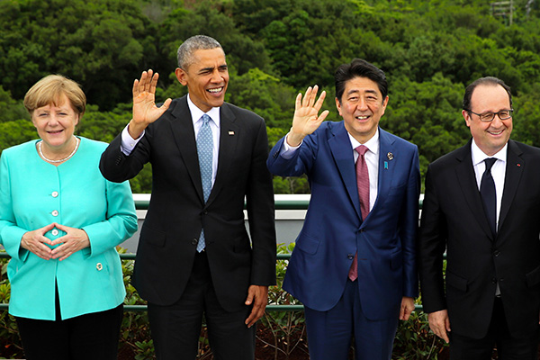 Japanese Prime Minister Shinzo Abe, second right, and U.S. President Barack Obama, second left, wave as German Chancellor Angela Merkel, left, and French President Francois Hollande smile during a group photo session with other leaders of Group of Seven industrial nations on the first day of the G-7 summit meetings in Shima, Japan, Thursday, May 26, 2016. (Japan Pool via AP) JAPAN OUT