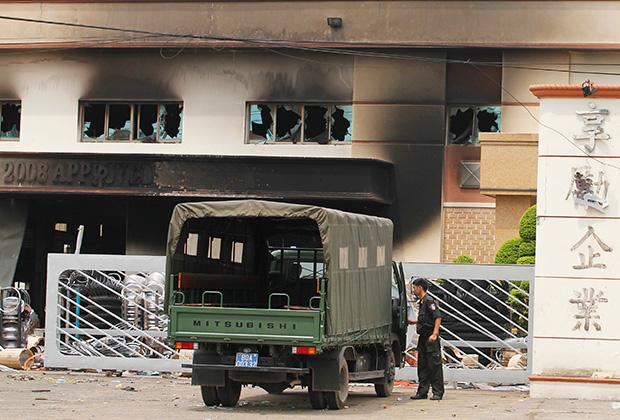Полицейские возле здания компании, разгромленной во время антикитайских выступлений. 16 мая 2014