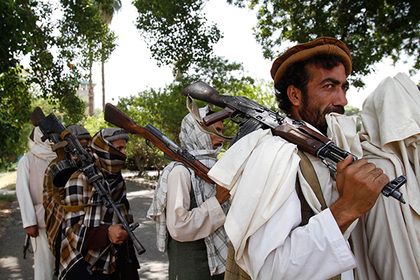 Taliban fighters hold their heavy and light weapons before surrendering them to Afghan authorities
