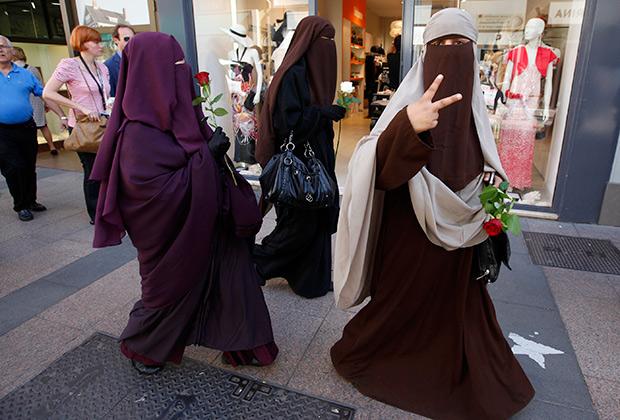 Три женщины идут на демонстрацию против запрета паранджи во Франции, 17 мая 2011 года
