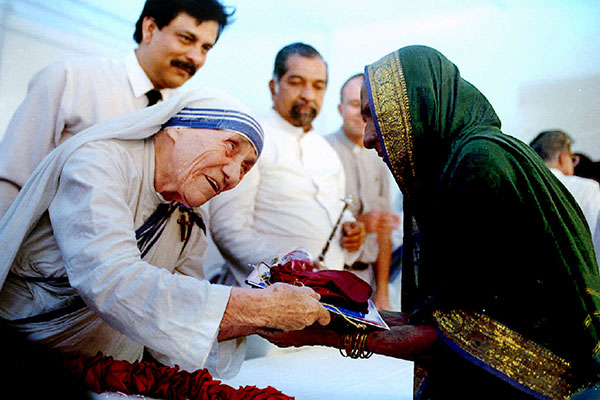 Mother Teresa presents documents for a new house to a villager from Latur in Bombay on September 26. More than a thousand people were rendered homeless in the earthquake that devastated Latur and surrounding villages killing over 10,000 people almost a year ago