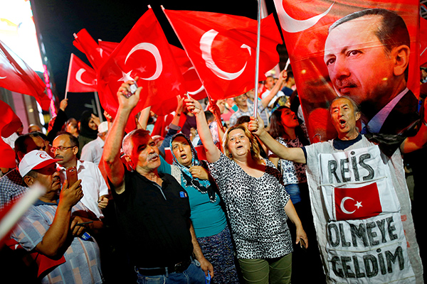 "People shout slogans and wave Turkish national flags as they have gathered in solidarity night after night since the July 15 coup attempt in central Ankara, Turkey, July 27, 2016. The banner on the right reads ""Chief (Erdogan) I came to die"". REUTERS/Umit Bektas"