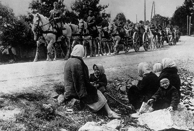 Немецкие солдаты проезжают мимо советских крестьян, выгнанных из своих домов. Август 1942 года