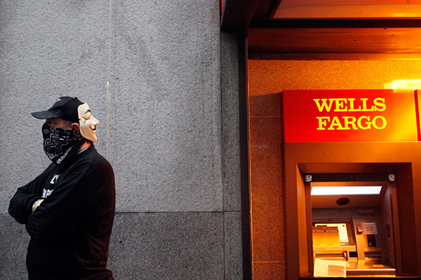 "SAN FRANCISCO - JANUARY 20:  An ""Occupy Wall Street West"" protestor from San Francisco, California. stands near an ATM machine at a Wells Fargo bank in the financial district as part of a day of action January 20, 2012 in San Francisco, California.  Occupy Wall Street West protestors blockaded all the entrances to the bank as part of a day of action.  (Photo by Sarah Rice/Getty Images)"