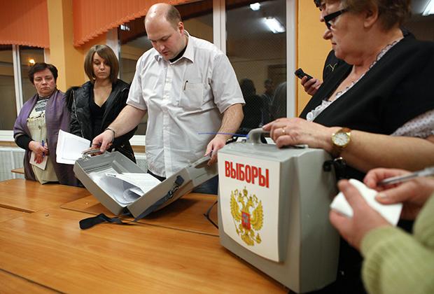 Сотрудник участковой избирательной комиссии вскрывает переносную урну для подсчета голосов