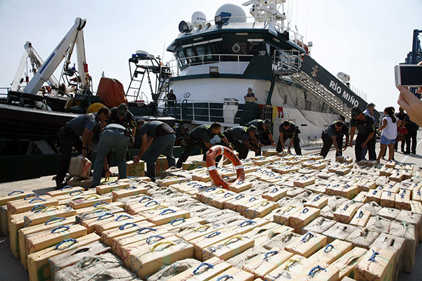 epa04416744 Spanish Civil Guard officers display bundles containing 13,000 kilo (13 metric tons) of hashish in Melilla, a Spanish enclave in northern Africa, on 25 September 2014. The drug was seized during a police operation in the Alboran Sea, the westernmost part of the Mediterranean Sea.  EPA/F.G. Guerrero
