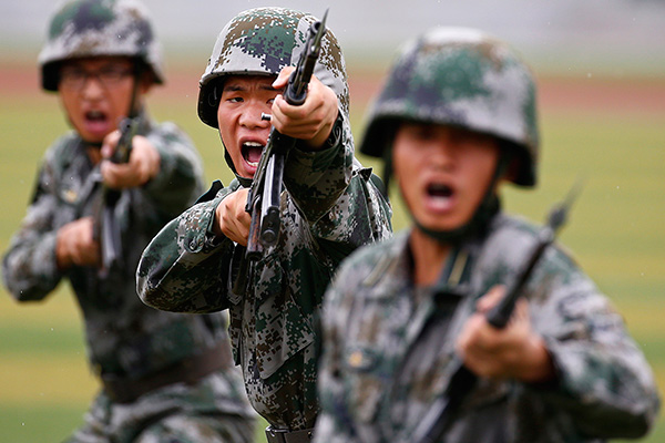 People's Liberation Army (PLA) soldiers shout as they hold guns and practise in a drill during a organized media tour at a PLA engineering school in Beijing, July 22, 2014. REUTERS/Petar Kujundzic (CHINA - Tags: MILITARY TPX IMAGES OF THE DAY) - RTR3ZLIT