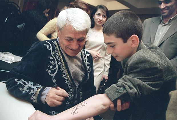 Дживан Гаспарян оставляет автограф на руке поклонника