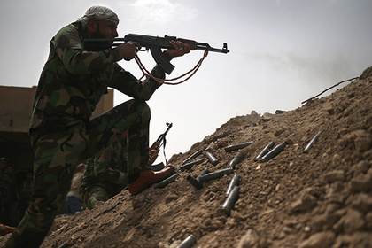 A volunteer from the Badr Brigade militia fires on ISIS fighters from the frontline on April 11, 2015 in Ebrahim Ben Ali, in Anbar Province, Iraq. Shia militia and Iraqi government troops are preparing for an assault on ISIS forces in Anbar, much of which was captured by ISIS forces last year.