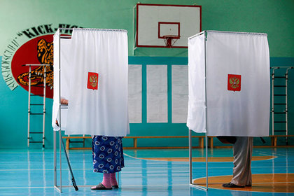 People stand inside voting booths as they visit a polling station during a parliamentary election in Stavropol, Russia, September 18, 2016. REUTERS/Eduard Korniyenko - RTSO8KD