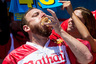NEW YORK, NY - JULY 4: Joey Chestnut competes in the annual Hot Dog Eating Contest at Coney Island July 4, 2016 in New York City. Joey Chestnut re-took the crown, eating 70 hot dogs and beating last year's winner Matt Stonie's 53 hot dogs consumed.