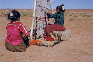 Two Navajo women use a loom to weave, Monument Valley, Arizona, undated