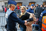 Residents of the Brussels suburb of Molenbeek are searched by police before taking part in a memorial gathering to honour the victims of the recent deadly Paris attacks, in Brussels, Belgium
