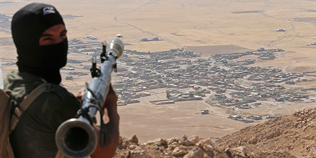 A Kurdish Peshmerga fighter holds a a rocket-propelled grenade launcher as he takes up position in an area overlooking Baretle village (background), which is controlled by the Islamic State, in Khazir, on the edge of Mosul September 8, 2014.