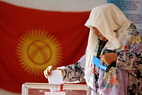 An ethnic Uzbek woman casts her ballot at a polling station in Osh, southern Kyrgyzstan, Sunday, June 27, 2010. Polls opened in violence-wracked Kyrgyzstan for a referendum Sunday to choose a new constitution that the interim government hopes will legitimize its power until new parliamentary elections in October.