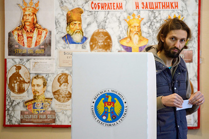 A man is about to cast his ballot for the presidential election at a polling station in Chisinau city on October 30, 2016. Ex-Soviet Moldova went to the polls on Ocotber 30 in its first popular presidential election since the 1990s, seen as a tug-of-war between supporters of closer relations with Russia and those seeking EU integration.