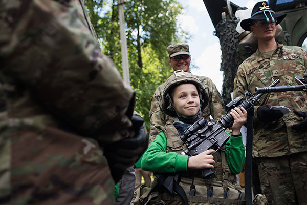 A young boy pose for photo with members of US Army's 2nd Cavalry Regiment during the ''Dragoon Ride II'' military exercise in Kupiskis some 160 kms (100 miles) north of the capital Vilnius, Lithuania, Sunday, June 12, 2016. The 2nd Cavalry Regiment is conducting Dragoon Ride II in order to test mission command, sustainment and freedom of movement of its Stryker Combat Vehicles over a 2,200-kilometer route. Dragoon Ride II begins in Germany and progresses along two routes through the Czech Republic, Poland, Lithuania and Latvia, and concludes in Estonia.