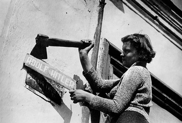Женщина снимает табличку с надписью «Адольф Гитлер». Конец Второй мировой войны