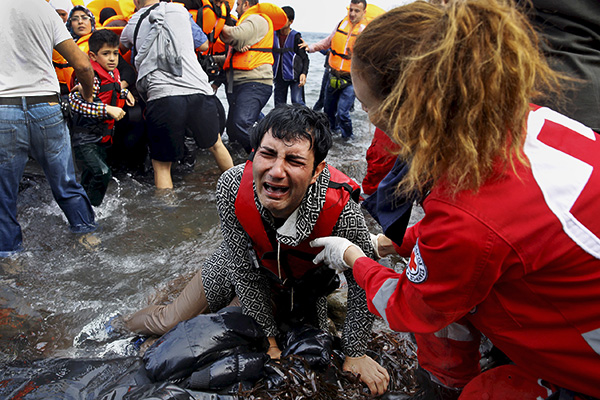 A Greek Red Cross volunteer comforts a crying Syrian refugee moments after disembarking from a flooded raft at a beach on the Greek island of Lesbos after crossing a part of the Aegean Sea from the Turkish coast on an overcrowded raft October 20, 2015.Thousands of refugees - mostly fleeing war-torn Syria, Afghanistan and Iraq - attempt daily to cross the Aegean Sea from nearby Turkey, a short trip but a perilous one in the inflatable boats the migrants use, often in rough seas.Almost 400,000 people have arrived in Greece this year, according to the U.N. refugee agency UNHCR, overwhelming the cash-strapped nation's ability to cope.