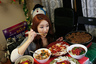 Park Seo-yeon, 34, eats in front of a video camera during her eating show in her apartment in Incheon, west of Seoul January 22, 2014. Known as The Diva, Park broadcasts for up to three hours every day from her apartment, where she eats alone as thousands of viewers watch and chat with her in real time over the Internet. South Korea's latest fad - gastronomic voyeurism - offers surprising amounts of money to thousands of online diners while serving up a sense of community in the wealthy Asian country's increasingly solitary society.