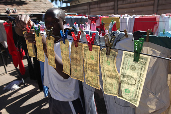 Alex Mupondi, hangs one dollar notes on a drying line after washing them in Harare, Zimbabwe, Tuesday, July 6, 2010. The washing machine cycle takes about 45 minutes _ and George Washington comes out much cleaner than before in Zimbabwe-style laundering of dirty money. Zimbabweans trading in the American currency since their own hyperinflationary notes were abandoned last year say washing their dirtiest cash works.(AP Photo/Tsvangirayi Mukwazhi)