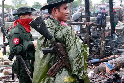 Бирманские солдаты на руинах сожженного дома в столице штата Ракхайн