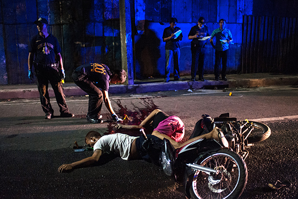 MANILA, PHILIPPINES - OCTOBER 3: (EDITORS NOTE: Image contains Graphic Content) Police investigators examine the bodies of two men who died in an alleged shootout with police on October 3, 2016 in Manila, Philippines. The Duterte administration shifted to the next phase on its war on drugs after the first 100 days of President Rodrigo Duterte as over 3,700 people have been killed while more than 700,000 drug dependents surrendered to authorities. According to reports, Duterte received an 'excellent' rating for his war on drugs during a recent opinion, with 84 percent of Filipinos respondents said they are satisfied with the drug crackdown.